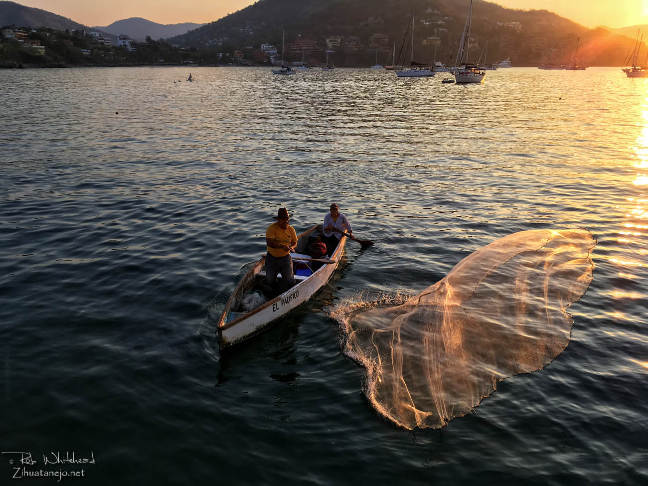 Fisherman casts net from canoe, Zihuatanejo